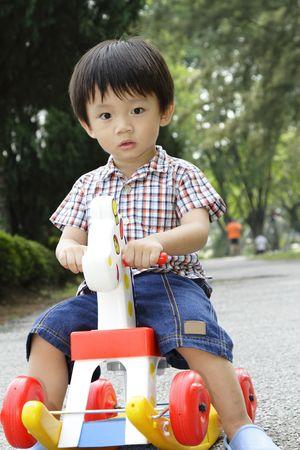 A cute Asian boy sitting on a rocking horse in a park
