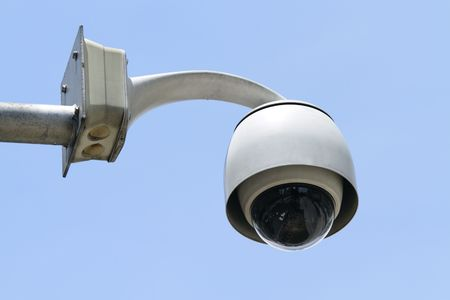A dome-type security camera against a clear blue sky photo