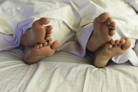 A pair of feet of a couple in bed