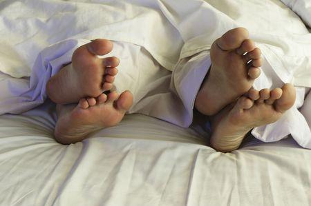 pareja durmiendo: Un par de pies de la cama en un par