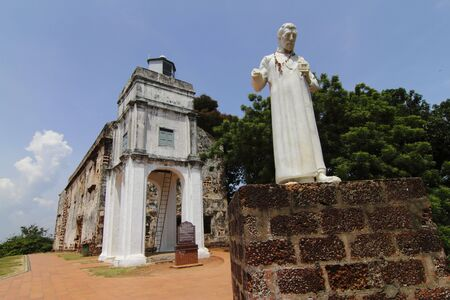 Exterior view of St. Paul's Church in Malacca, Malaysia with a statue of St. Francis Xavier in front Stock Photo