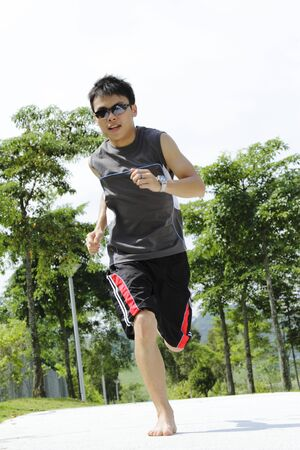 A young Asian man jogging barefoot at a public park Stock Photo