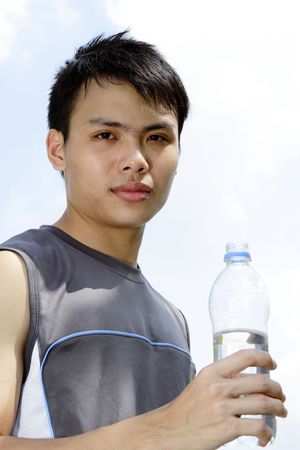 A young Asian man drinking water after a workout session photo