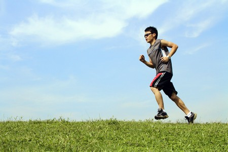 and the horizontal man: A young Asian man running on grass Stock Photo