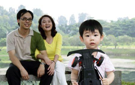 public park: Un ni�o asi�tico con su familia en un parque p�blico