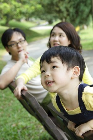 An Asian child at a bench with his parents in the background photo