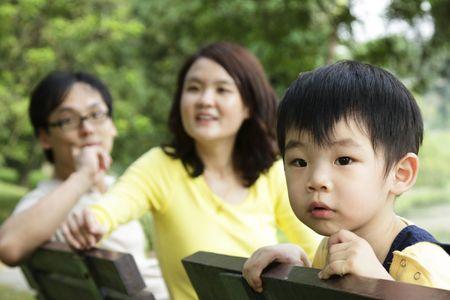 asia family: Un ni�o asi�tico en un banco con sus padres en segundo plano