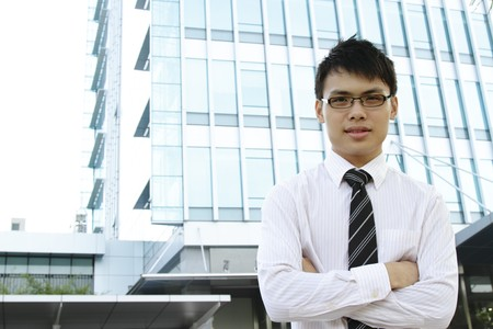 An Asian business executive standing in front of an office building