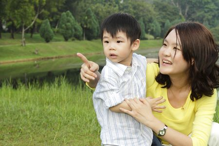 An Asian mother and her son at a public park