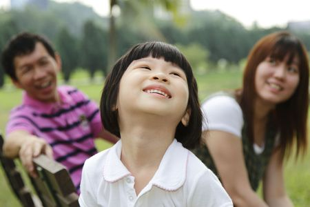 A happy Asian family at a park