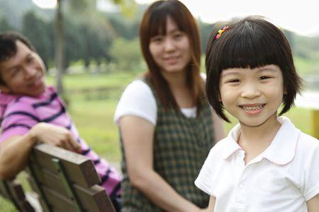 A happy Asian family at a park photo
