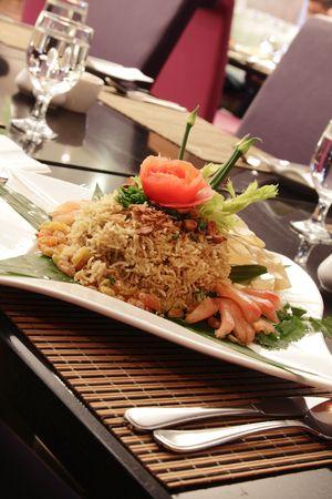 A plate of Malaysian fried rice with garnishing, herbs, sliced tomato, raisins and banana leaf