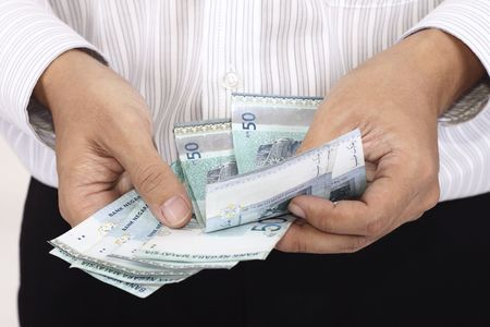 man holding money: An Asian man counting some cash