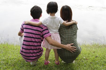 Rear view of an Asian family by a lake