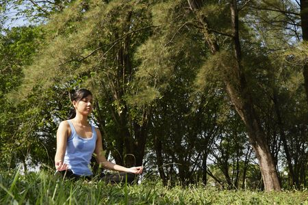 An Asian woman doing some yoga exercise at a  forest photo