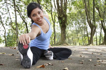 An Asian woman performing some stretching exercise at a park