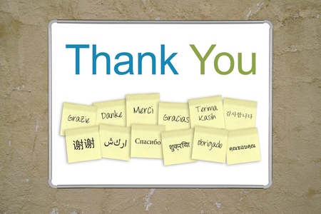 """A whiteboard with the words """",thank you"""", in 13 different languages."""