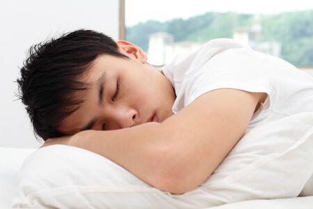 An Asian man sleeping on a bed