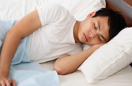 An Asian man sleeping on a bed photo