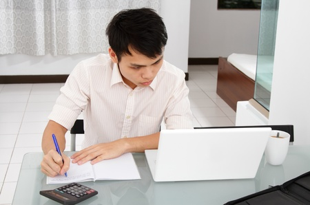 calculator chinese: An Asian college student doing homework at home
