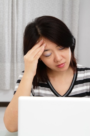 An Asian woman having a headache