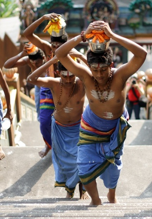BATU CAVES, MALAYSIA - JANUARY 21:A group of teenagers carrying pots of milk during the Hindu festival of Thaipusam on January 21, 2011 in Batu Caves, Malaysia.