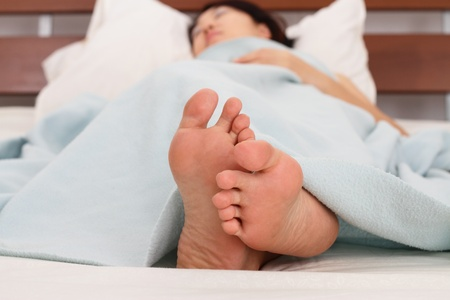 feet in bed: Close-up of a womans feet Stock Photo