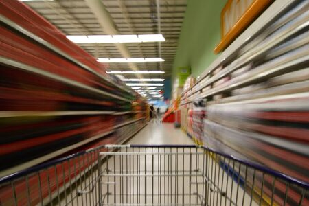 supermarket shelves: A supermarket scene with shopping cart and motion blur Stock Photo