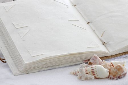A blank page of a photo album made of recycled paper to paste memories of a day at the seaside or holiday on a towel with seashells in the foreground