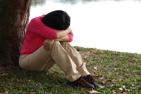 A depressed Asian woman sitting by a tree photo