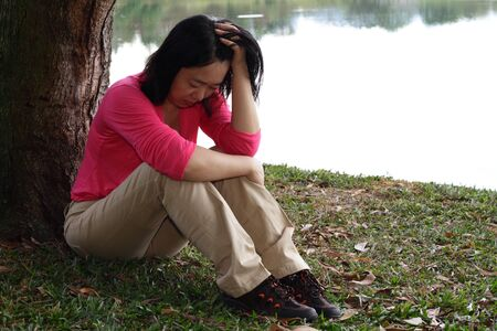 A depressed Asian woman sitting by a tree Stock Photo