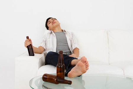 A drunk man on a sofa with beer bottles
