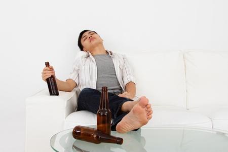 ubriaco: Un uomo ubriaco su un divano con le bottiglie di birra Archivio Fotografico
