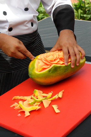 papaya flower: A chef carving flower shapes out of a papaya fruit Stock Photo