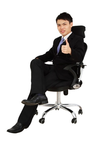 An Asian executive showing thumbs up while sitting on a chair and isolated in white background photo