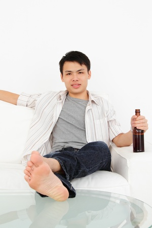 An Asian man watching TV with a bottle of beer photo