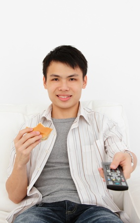 A young Asian man with a TV remote and burger photo