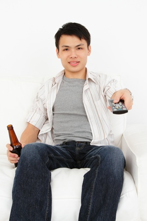 tv remote: A young Asian man with a TV remote and bottle of beer