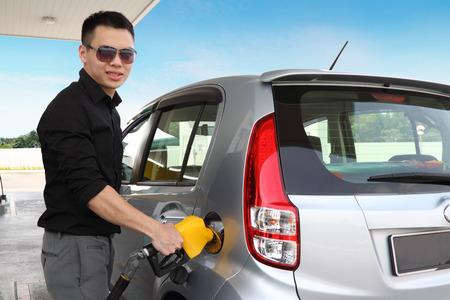 estacion de gasolina: Un joven repostar su coche Foto de archivo