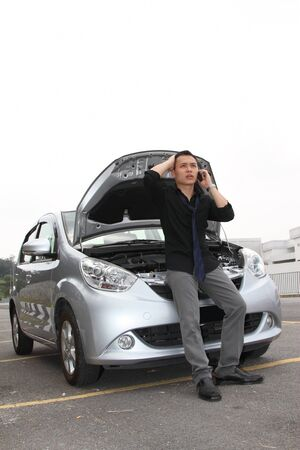 breakdown: A man standing in front of a stalled car