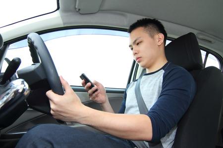Un conductor varón mensajes de texto en un teléfono celular mientras se conduce Foto de archivo