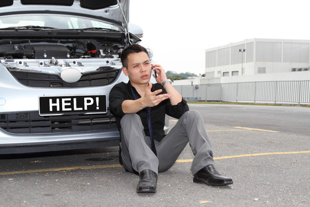 A man calling for help to repair a stalled car photo
