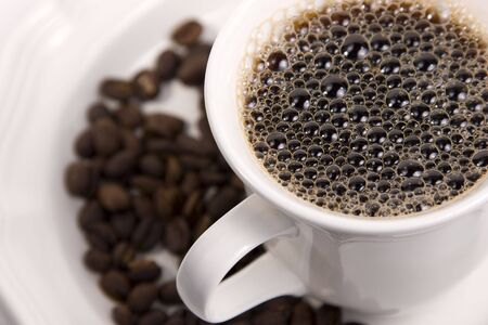 Cup of Black Coffee on a saucer of whole beans with selective focus on bubbles