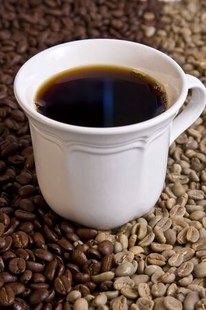 Cup of Black Coffee sitting in Whole Roasted and Green Beans