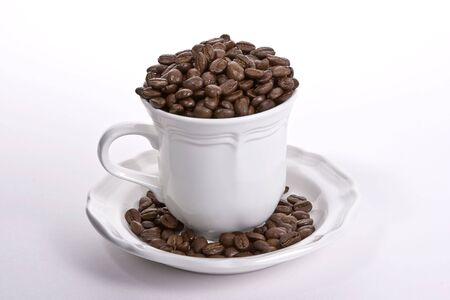 White coffee cup on a white saucer full of whole coffee beans spilling over