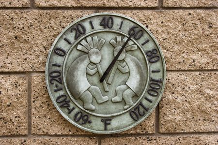 Backyard Kokopelli wall thermometer on brick background