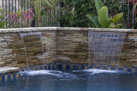 Swimming pool waterfall and beautiful foliage Stock Photo