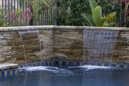 hardscape: Swimming pool waterfall and beautiful foliage Stock Photo