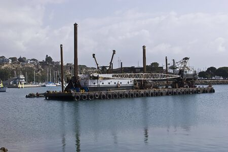 Dredging machine anchored in the harbor Stock Photo