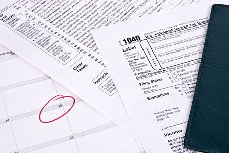 Income tax return, checkbook  and calendar showing due date Stock Photo